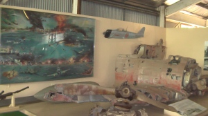 Painting of the February 19, 1942 raid on Darwin, with remnants of a Zero that was shot down. The Zero was piloted by Sergeant Toyoshima who was later captured. Photo by D. Dears.