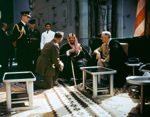 Meeting between King Saud and President Roosevelt. Admiral Leahy to the left, Colonel Eddy, interpreter and head of US Legation, Jeddah SA, kneeling.